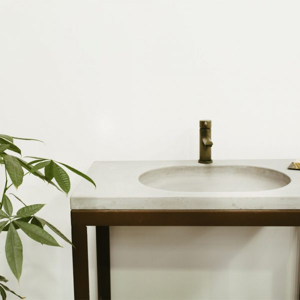 An oval concrete sink set into a vanity top with aged brass tap - MARLEE by Concrete Studio