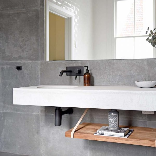 Bowl shaped floating concrete sink in a modern bathroom with matte black taps