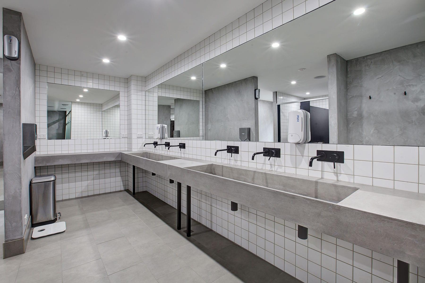 Concrete Ramp Sinks - whole bathroom view - by Concrete Studio